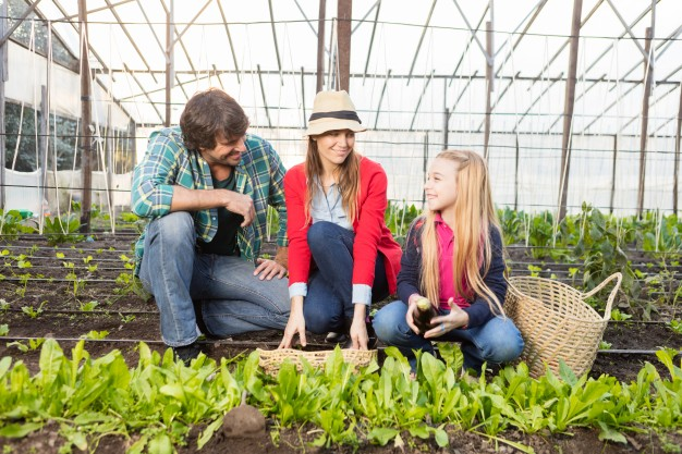 parents-with-her-daughter-in-a-greenhouse_23-2147562460
